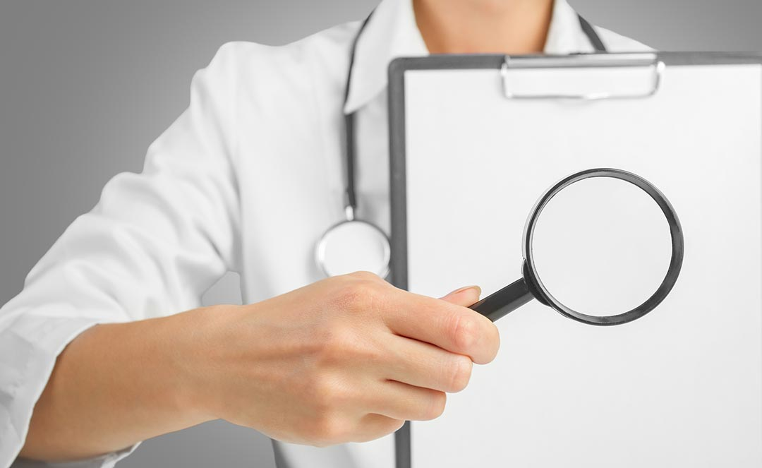 Image of a doctor holding a magnifying glass and report